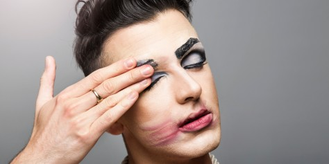 Cross dresser smearing makeup of face